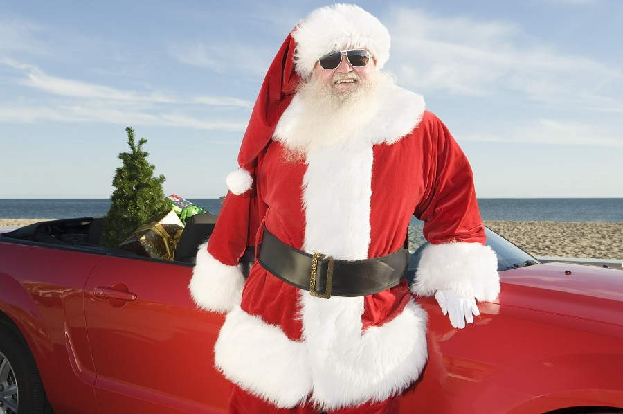 santa claus stands by red convertible