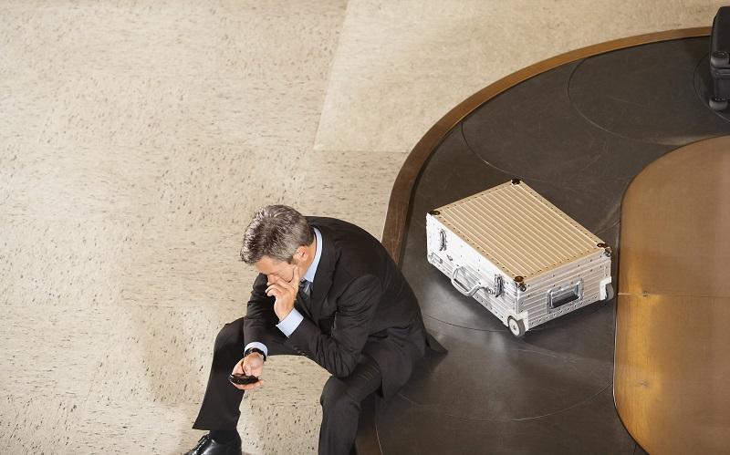 man sitting on luggage carousel